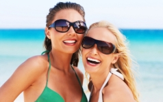 Young women at beach, smiling, portrait